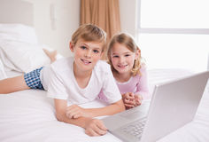 Siblings using a laptop Stock Photos
