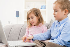 Siblings using laptop computer Stock Photography