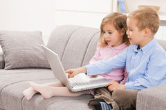 Siblings using laptop computer Stock Images
