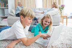 Siblings using laptop on the floor Stock Photography