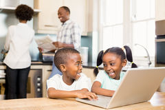 Siblings using laptop in kitchen. Siblings using laptop against parents in kitchen stock photography