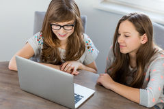 Siblings using laptop together at home Royalty Free Stock Photos