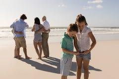 Siblings using mobile phone stock photo
