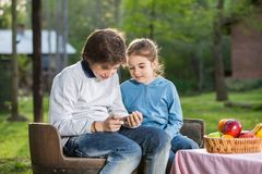 Siblings Using Smartphone At Campsite Stock Photo