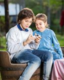 Siblings Using Smartphone At Campsite Royalty Free Stock Images