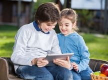 Siblings Using Tablet Computer At Campsite Royalty Free Stock Photos
