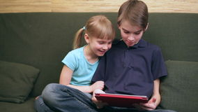 Siblings using a tablet computer stock video footage