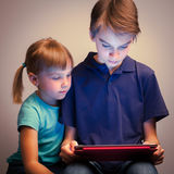 Siblings using a tablet computer. Children wearing casual clothes playing or watching a movie on a touch pad at home. Boy and girl are half-siblings. Brother is Royalty Free Stock Image