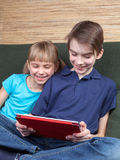 Siblings using a tablet computer Stock Photography