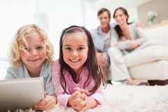 Siblings using a tablet computer while their parents are in the Royalty Free Stock Image