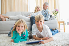 Siblings using tablet pc on the floor Royalty Free Stock Photo