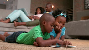 Siblings using tablet pc on the floor stock video footage