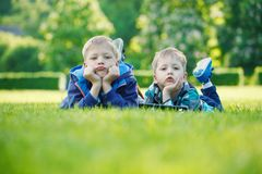Siblings using a tablet, yingon grass in the park in suny day.  Royalty Free Stock Photography