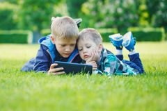 Siblings using a tablet, yingon grass in the park in suny day.  Stock Photo