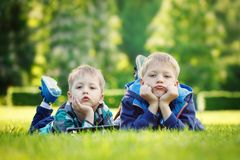 Siblings using a tablet, yingon grass in the park in suny day.  Royalty Free Stock Image