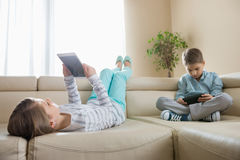 Siblings using technologies on sofa at home Stock Photo