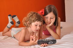 Siblings on vacation. Rest and play on the console Royalty Free Stock Photos