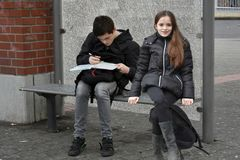 Siblings waiting at school bus stop royalty free stock photography