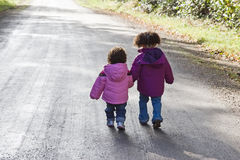 Siblings Walking. Two toddler sisters walking hand in hand down a roadway Stock Images