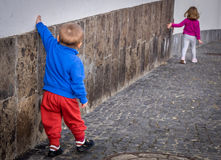 Siblings walking along the wall Royalty Free Stock Photography