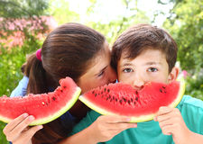 Siblings with water melon slices Stock Photo