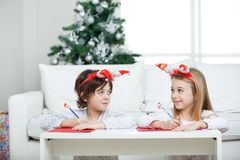 Siblings Writing Letter To Santa Claus During Stock Photo
