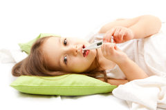 Sic little girl on bed with thermometer Stock Photo