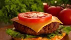 Sice des chutes de tomate sur l'hamburger banque de vidéos