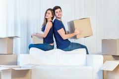 Sich bewegen, Reparaturen, neue Wohnung Ein liebevolles Paar, das Kasten in h hält Stockfotografie