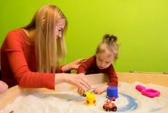 Sich entwickelnde Studien der weißen europäischen Leute der Mutter und der Tochter der frühen Entwicklung mit Sand im Sandkasten  Stockbild