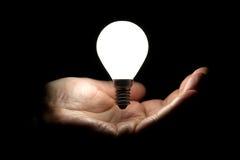 Sich hin- und herbewegende Glühlampe über Hand auf schwarzem Hintergrund Stockfoto
