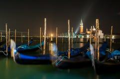 Sich hin- und herbewegende Gondeln nachts mit Kirche von maggiore Sans Giorgio Stockfoto