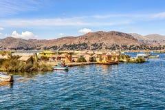 Sich hin- und herbewegende Inseln gemacht von den Schilfen auf Titicaca-See unter blauem Ski stockbild