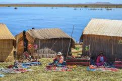 SICH HIN- UND HERBEWEGENDE INSELN UROS, PUNO, PERU 31. MAI 2013: Traditionsgemäß gekleidete Aymara Uros-Leute leben auf diesen In Stockbilder
