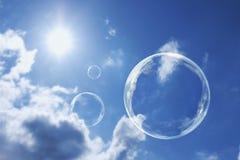 Sich hin- und herbewegende Seifenblasen gegen klaren sonnenbeschienen blauen Himmel und Wolken Stockbilder