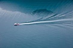 Sich hin- und herbewegendes Boot auf dem blauen Fjord in Norwegen Stockbilder