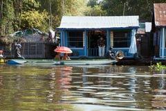 Sich hin- und herbewegendes Dorf, buddhistische Mönche, die Häuser durch Boot besichtigen lizenzfreie stockbilder