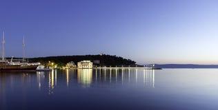 Sich hin- und herbewegendes Schiff mit Hotel Osejava im Hintergrund - Makarska, Kroatien Stockfotografie