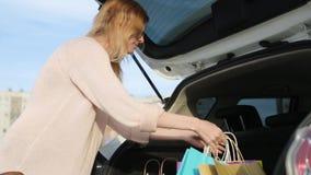 Sich nach dem Einkauf eine junge Frau mit Taschen freut Shopaholic Blondine betrachten ihre K?ufe im Stamm von stock video