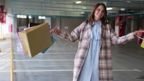 Sich nach dem Einkauf junge Frau mit Taschen freut Brunette Frau mit mehrfarbigen Paketen nahe bei dem Speicher Verkauf herein stock video