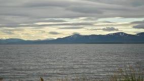 Sich schnell bewegende Wolkenschicht über majestätischen Bergen und blauer Fjord wässern timelapse stock footage