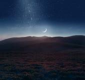 Sichelförmiger Mond über den Bergen Stockfotografie