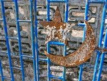 Sichelförmiges Symbol des rostigen Sternes befestigt zum blauen Stahltor am Eingang einer alten Moschee lizenzfreies stockfoto
