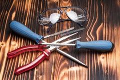 Sicherheit googelt, Brillen mit Zangen, Schraubenzieher, Sägeblätter lizenzfreies stockfoto