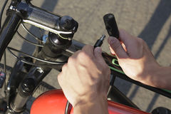 Sicherheit und Transport - nah oben vom Mannbefestigungs-Fahrradverschluß auf Straßenparken Lizenzfreies Stockbild