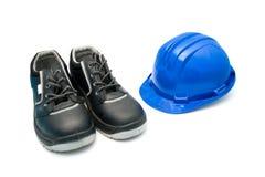Sicherheits-Schuhe und blauer Sturzhelm Stockfoto