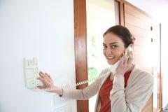 Sicherheits-Türtelefon der Frau antwortendes stockfotos