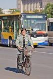 Sicherheitsbeamte auf seinem Fahrrad mit Bus auf dem Hintergrund, Peking, China Stockfotografie