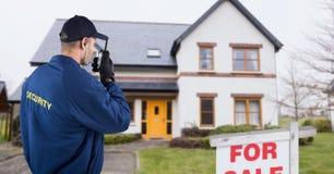 Sicherheitsbeamte, der auf Funksprechgerät bei der Stellung auf Straße spricht Lizenzfreie Stockfotos
