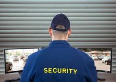 Sicherheitsbeamte, der das Bild der Überwachungskameras schaut Blinder Hintergrund Stockfotos